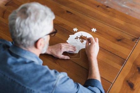 Oberflächliche Ansicht eines älteren Mannes auf verschwommenem Vordergrundfaltpuzzle auf Tisch