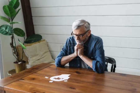 Photo for Pensive senior man looking at jigsaw on table - Royalty Free Image