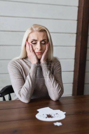 Traurige ältere Frau mit Demenz sitzt neben verschwommenem Puzzle auf Tisch