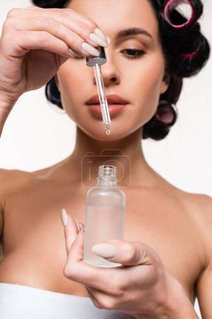 serum bottle and pipette with drop in hands of young woman isolated on white