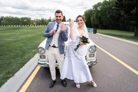 Cheerful newlyweds showing rings near retro auto on road