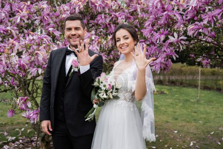 Smiling bride and groom showing rings near magnolia trees