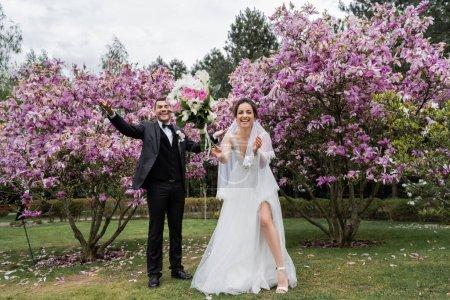 Photo pour Heureux jeunes mariés debout près de bouquet de chute dans le parc - image libre de droit