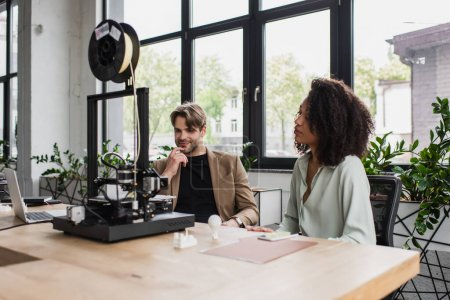 Photo for Young interracial designers sitting near 3D printer, plastic figures and laptop in modern open space - Royalty Free Image