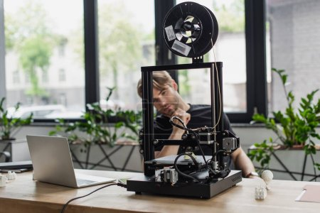 Photo for Young designer looking at 3D printer on table with laptop in office - Royalty Free Image
