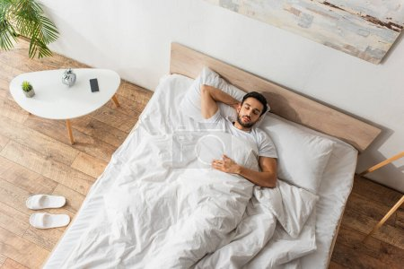 Top view of man sleeping on bed near slippers and smartphone in bedroom