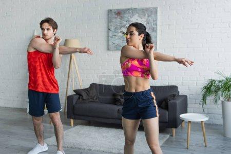 Photo pour Jeune couple en vêtements de sport échauffement avant l'entraînement à la maison - image libre de droit