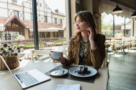 La mujer a la moda en las gafas que sostienen la taza cerca del postre sabroso y el portátil en la cafetería