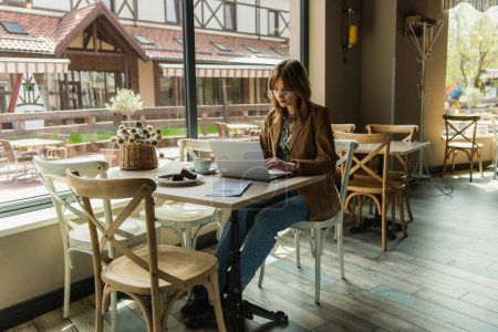 Stylish woman using laptop near dessert and coffee in cafe