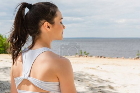 Photo for Young brunette woman with closed eyes meditating near sea - Royalty Free Image
