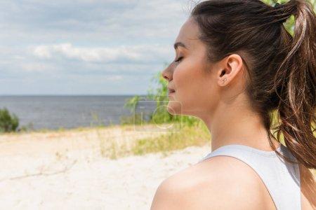 junge und brünette Frau mit geschlossenen Augen meditiert in der Nähe des Ozeans