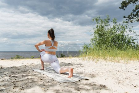 back view of brunette woman stretching on yoga mat on sand