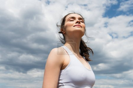 low angle view of young woman with closed eyes against blue sky with clouds