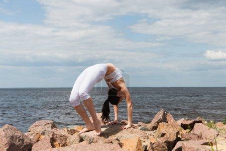 brunette woman standing in wheel pose on stones near sea