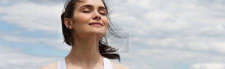 Photo pour Jeune femme heureuse contre le ciel bleu avec des nuages, bannière - image libre de droit