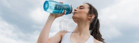 Photo pour Vue de bas angle de la jeune femme dans l'eau potable supérieure de culture contre le ciel bleu avec des nuages, bannière - image libre de droit