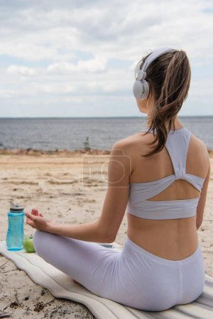 back view of young woman in headphones listening music while meditating on yoga mat