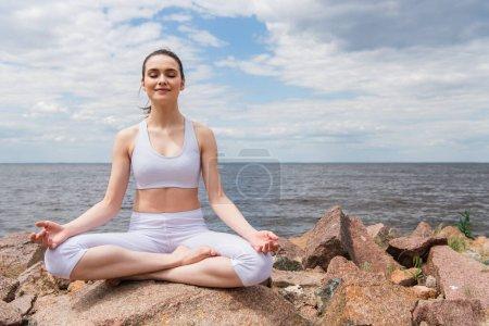 zufriedene junge Frau in Kopfhörern und Sportbekleidung, die in Lotus-Pose sitzt, während sie am Meer meditiert