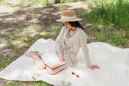smiling young woman in straw hat reading book in forest