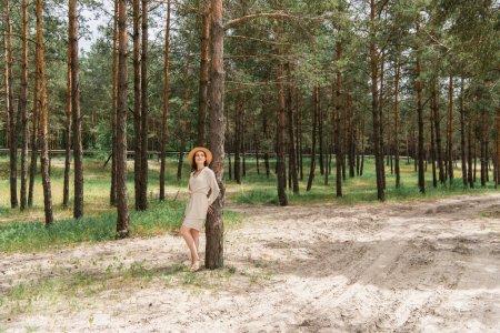 lebensfrohe junge Frau mit Strohhut, die im Wald steht