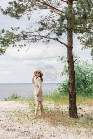 volle Länge der lächelnden jungen Frau mit Strohhut, die im Wald am See steht