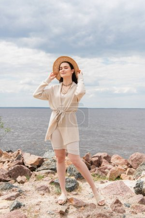 full length of smiling young woman adjusting straw hat and standing near sea