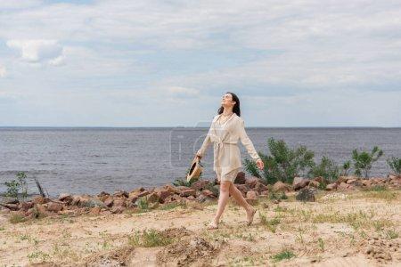 pleine longueur de sourire jeune femme tenant chapeau de paille et marchant près de la mer