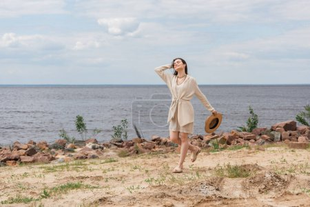 full length of happy young woman holding sun hat and walking near sea
