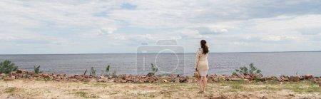 Photo pour Pleine longueur de brune jeune femme tenant chapeau de soleil et debout près de la mer, bannière - image libre de droit