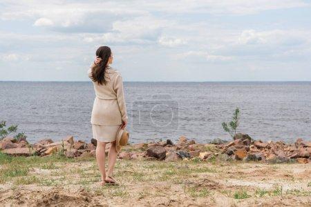pleine longueur de femme brune tenant chapeau de soleil et debout près de la mer