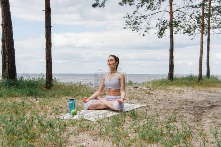 brunette woman in sportswear sitting in lotus pose and meditating on yoga mat