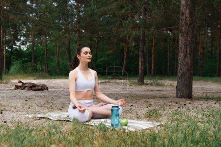 paisible jeune femme en vêtements de sport assis dans la pose de lotus et méditant sur tapis de yoga