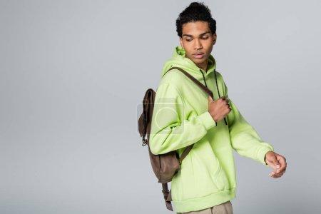 Photo pour Afro-américain avec sweat à capuche vert et sac à dos en cuir isolé sur gris - image libre de droit