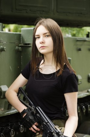 Girl with a gun, posing near the armored vehicle