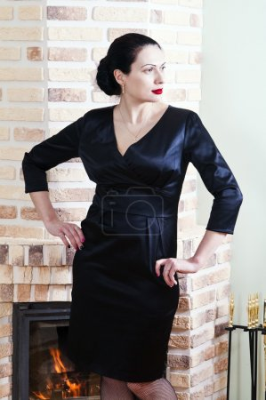 Woman in a black evening dress posing in the interior with a fireplace