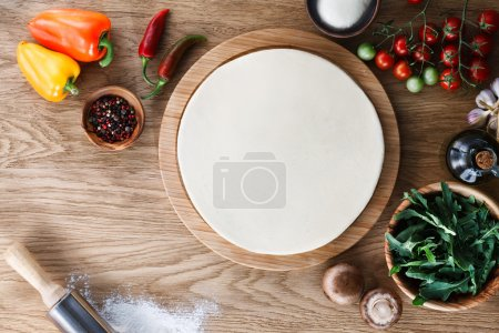 Photo for Fresh dough pizza base  and ingredients on a wooden textured table. Top view. - Royalty Free Image
