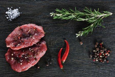 Photo pour Deux steaks de boeuf garnies de quelques brindilles de romarin, piment nain, granules de sel de mer et poivre sur un fond sombre. Vue de dessus. - image libre de droit