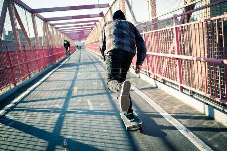 Skateboarder cruise on bridge