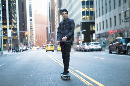 Young skateboarder cruising donw the city street before sunset