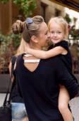 mother hugs her little daughter