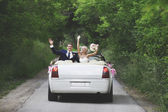 The groom and the bride in a convertible car