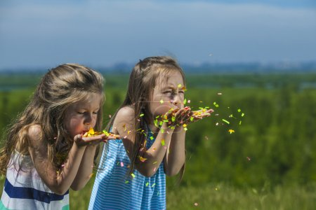 Children with confetti in hand inflate them in the wind