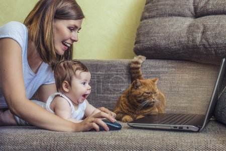 Photo pour La femme avec un bébé et un chat à l'ordinateur portatif se trouvant sur le divan - image libre de droit