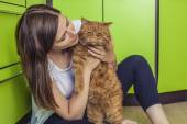 Woman with a ginger cat in her arms cuddling on the kitchen