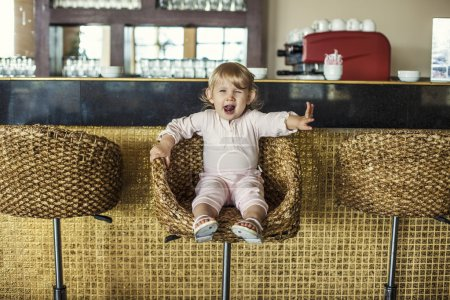 Beautiful baby in the cafe bar makes the order