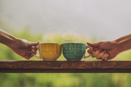 Hands holding mug with hot beverage, with tea on a wooden stand