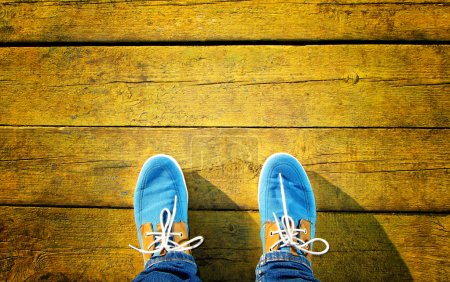 Men's blue shoes on a yellow surface
