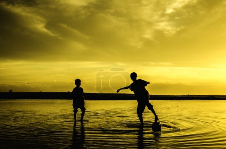 Image silhouette of two boys play beach soccer during sunset sunrise. blur on water and sky. reflect on water