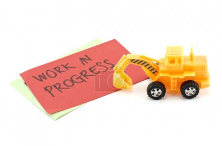 image concept yellow toy bulldozer with on color paper and blur word work in progress