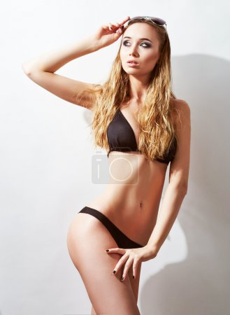 attractive slim girl in a swimsuit suit and sunglasses. studio